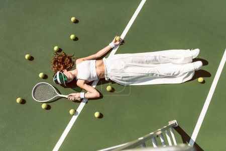 overhead view of stylish woman in white clothing and cap lying with racket lying on tennis court with racket