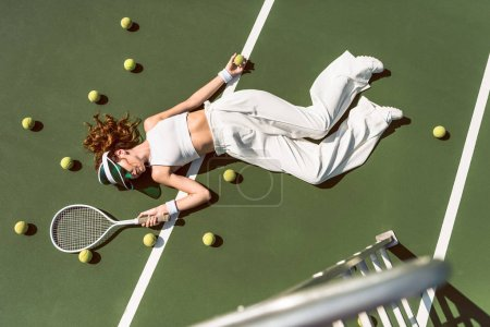 overhead view of attractive woman in white clothing and cap lying with racket lying on tennis court with racket