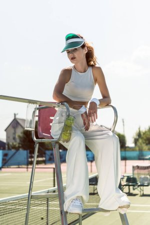 fashionable woman in white clothing and cap sitting on referee chair on tennis court