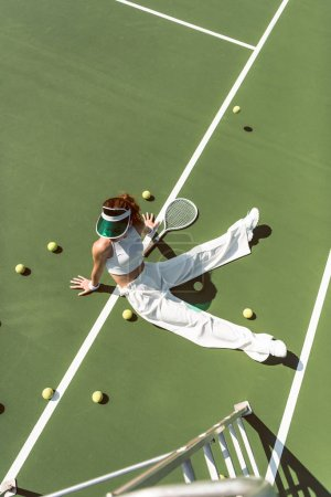 high angle view of beautiful woman in stylish white clothing sitting on tennis court with balls and racket around
