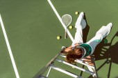 overhead view of woman in stylish white clothing and cap posing on referee chair on tennis court