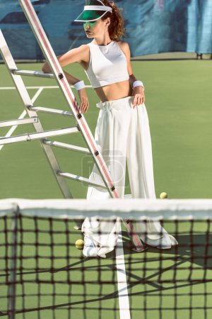 young woman in stylish white clothing and cap posing near referee chair on tennis court