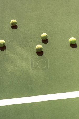 close up view of tennis balls on green tennis court