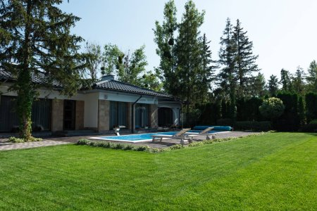 outside view of modern house, green lawn and poolside with sunbeds