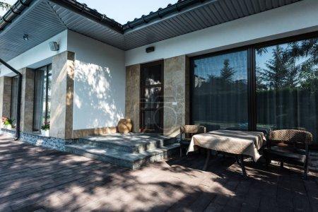 Photo pour Maison avec entrée de jardin avec table et fauteuils - image libre de droit
