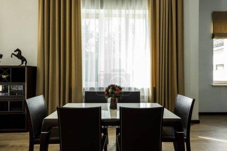 Photo pour Vue intérieure de la salle à manger élégante avec table, chaises et grande fenêtre - image libre de droit