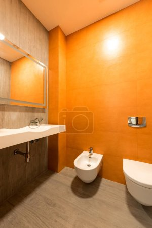 interior of modern bathroom in orange and white colors with toilet and bidet