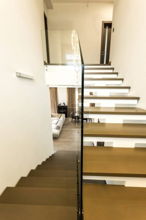 Photo for Interior view of modern stairs with glass railings to living room - Royalty Free Image