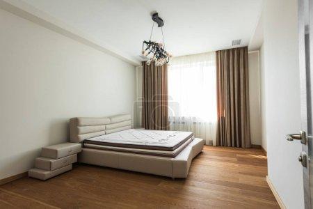 Photo pour Intérieur de la chambre vide avec grande fenêtre et matelas sur le lit - image libre de droit