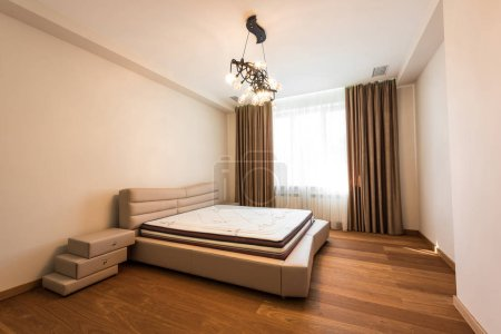 interior of stylish bedroom with big window and mattress on bed