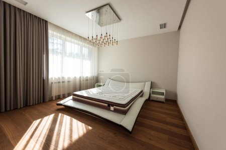 interior of modern bedroom with bed and light bulbs on ceiling