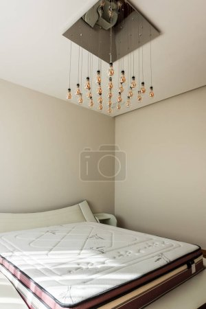 interior of stylish bedroom with bed and light bulbs on ceiling