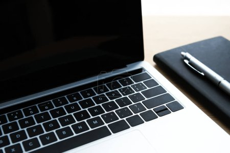 close-up view of laptop with blank screen, notebook and pen on table