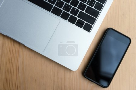 top view of laptop and smartphone with black screen on wooden table