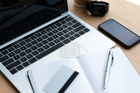 laptop, smartphone, smartwatch and blank notebook with pen and credit card on wooden table