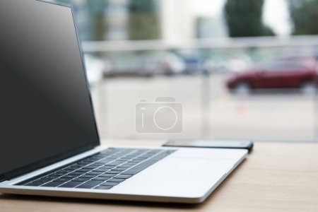 close-up view of laptop with black screen and smartphone on wooden table