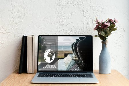 laptop with booking website on screen, books and flowers in vase on wooden table