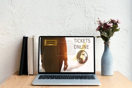laptop with tickets online website on screen, books and flowers in vase on wooden table