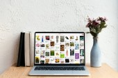 laptop with pinterest website on screen, books and flowers in vase on wooden table