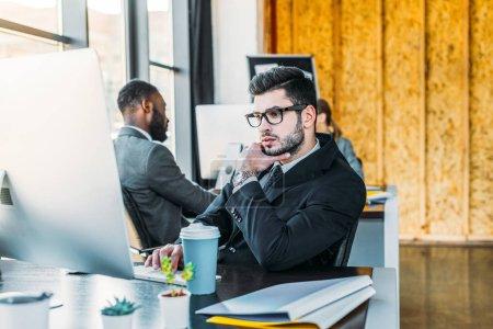 Photo pour Homme d'affaires pensif regardant d'ordinateur de bureau - image libre de droit