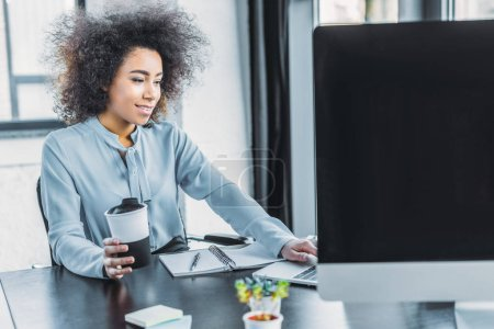 african american businesswoman holding cup of coffee and using laptop in office