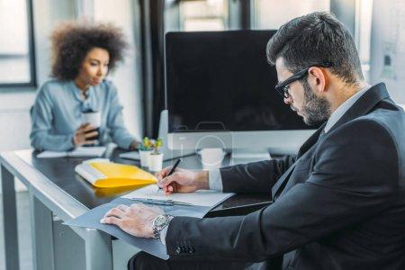 Photo pour Homme d'affaires multiculturel et femme d'affaires travaillant à table dans le Bureau - image libre de droit