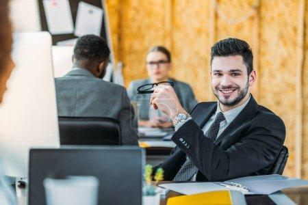 Photo pour Homme d'affaires souriant regardant la caméra dans le bureau - image libre de droit