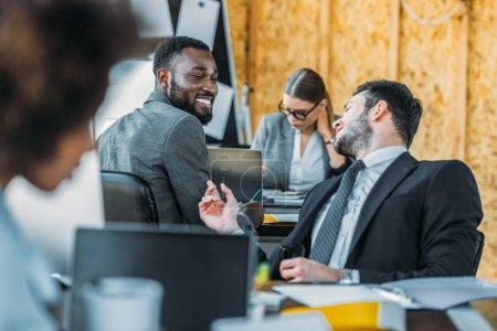smiling multicultural businessmen talking in office