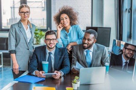 Lächelnde multikulturelle Geschäftsleute, die im Büro in die Kamera schauen