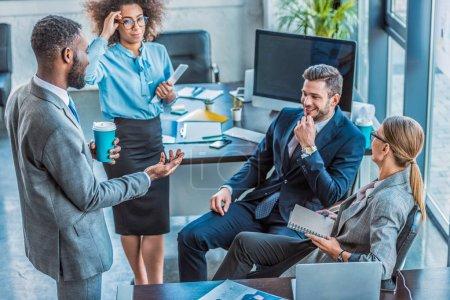 Foto de Empresarios multiculturales felizes hablando en la oficina - Imagen libre de derechos