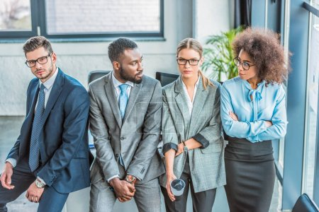 multicultural businesspeople leaning on table in office