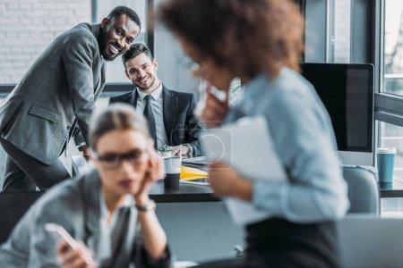 smiling multiethnic businessmen looking at businesswomen in office