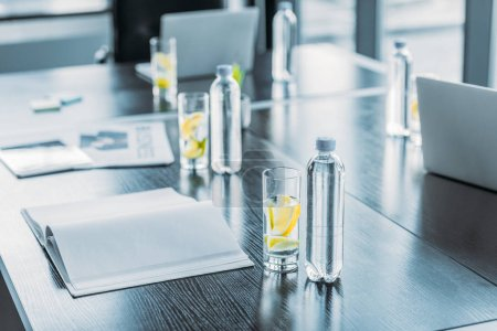 Photo for Bottles and glasses with antioxidant drink for business meeting on table in workspace - Royalty Free Image