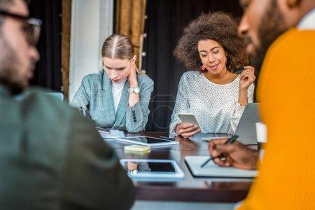 Photo pour Entrepreneurs multiculturelles avec les gadgets sur table au bureau - image libre de droit