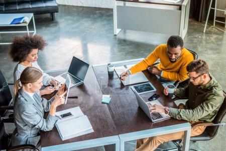 Foto de Vista de ángulo alto de empresarios multiculturales utilizando gadgets en la oficina - Imagen libre de derechos