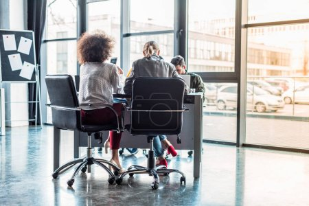 Photo for Rear view of multicultural businesspeople sitting at table in workspace - Royalty Free Image