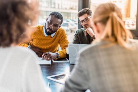 multicultural businesspeople sitting at table in office