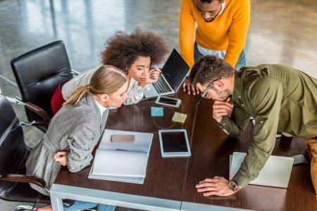 Photo pour Vue d'angle élevé de gens d'affaires multiculturelles regardant tablette Bureau - image libre de droit