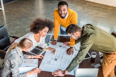 vue d'angle élevé de gens d'affaires multiculturelles en regardant blueprint en l'espace de travail