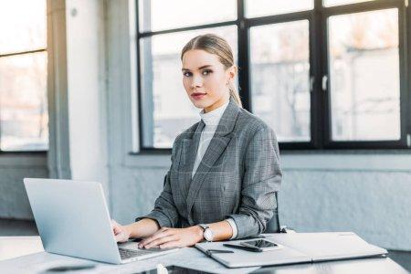 Photo pour Belle femme d'affaires utilisant l'ordinateur portable au bureau et en regardant la caméra - image libre de droit