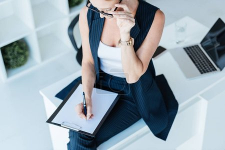 Photo for High angle view of businesswoman writing in clipboard on table with laptop in office - Royalty Free Image