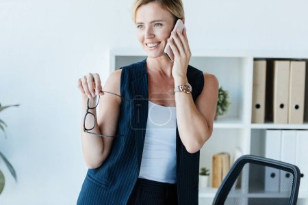 attractive smiling businesswoman holding eyeglasses and talking on smartphone in office