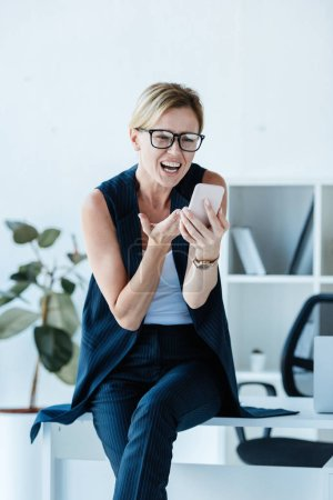 emotional businesswoman in eyeglasses gesturing during video call on smartphone in office