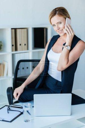 Photo pour Belle femme d'affaires, parler sur smartphone sur table avec ordinateur portable au bureau - image libre de droit