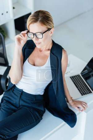 high angle view of attractive businesswoman sitting on table with laptop in office
