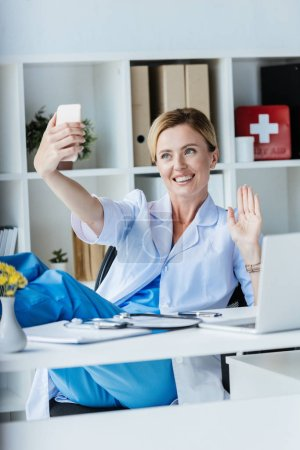 happy female doctor having video call on smartphone and waving by hand in office