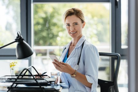 beautiful female doctor with smartphone in hand looking at camera and sitting at table in office