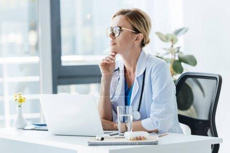 Photo pour Réfléchie femme médecin en lunettes assis à table avec ordinateur portable au bureau - image libre de droit