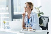 thoughtful female doctor in eyeglasses sitting at table with laptop in office