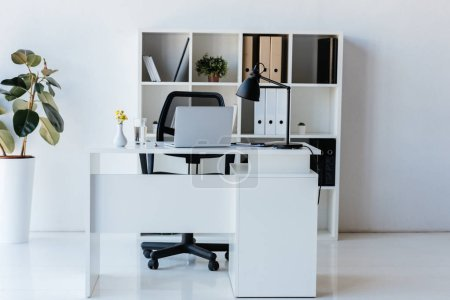 interior of modern office with table, laptop and shelves with folders